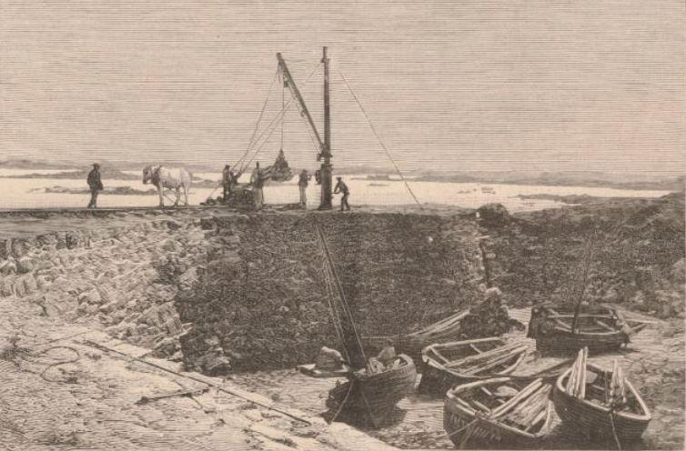 Petit port de l'île Vierge, avec le mât de charge et le treuil à main pour le débarquement des matériaux et les canots pour ramener les manœuvres à Plouguerneau