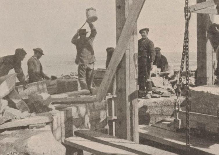 Les travaux à 45 m de hauteur en 1899, la tour creuse avec son escalier les parements sont en pierres de taille le rempli est de moellon et mortier, un ouvrier avec une masse en bois frappe une pierre pour la positionner
