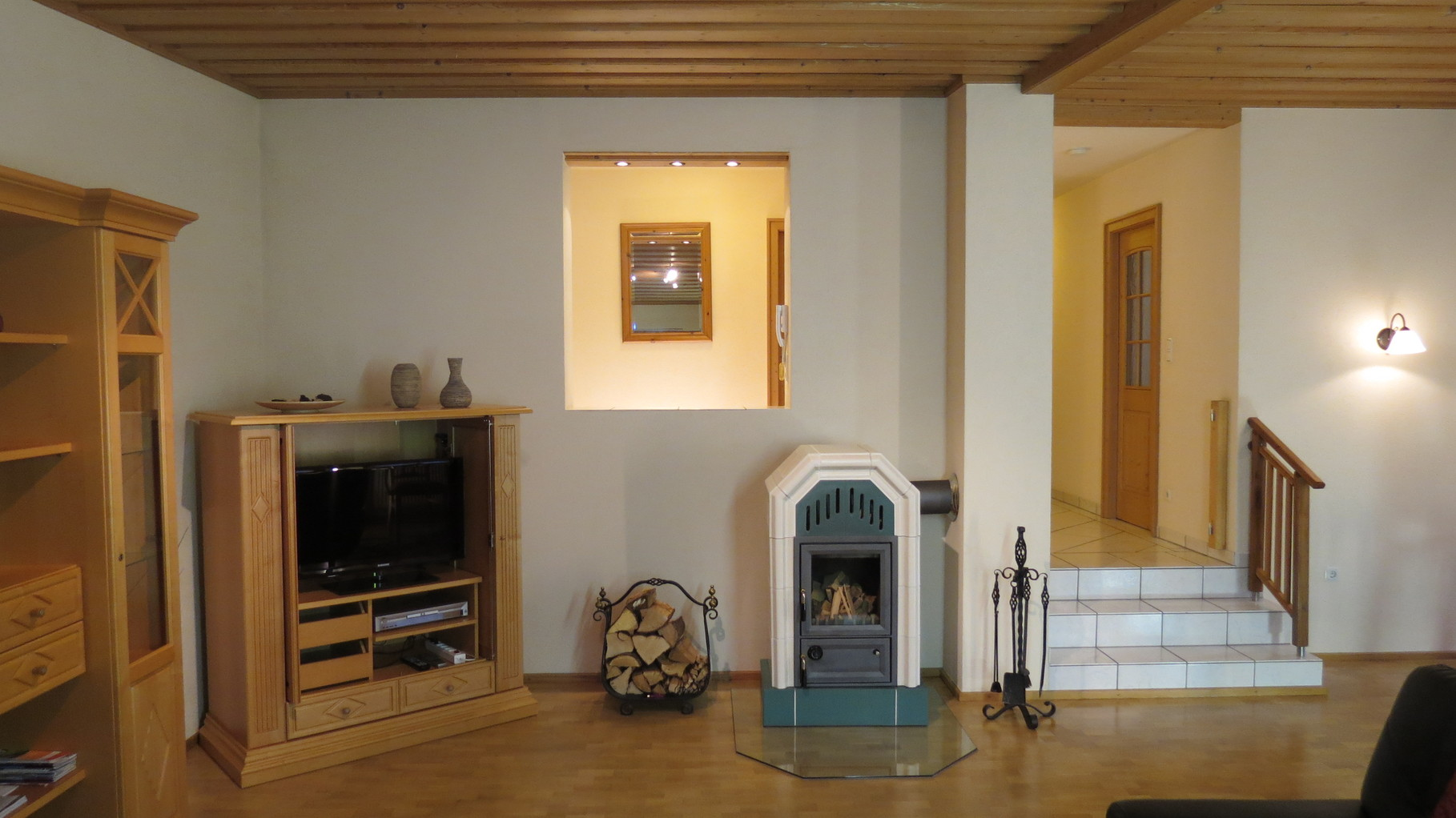 Wohnzimmer mit LED-Flachbild-TV und Kaminofen
