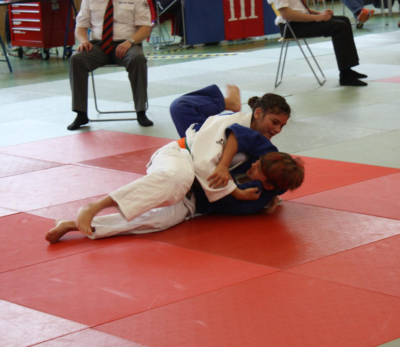 Tessa Dobrocky (weißer Judogi) hat geworfen und nimmt nun den Haltegriff ein.