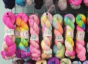 A row of multi coloured yarn skeins in vibrant pinks, greens, yellows.