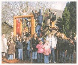 Kinder und Lehrer auf und am neuen Klettergerüst