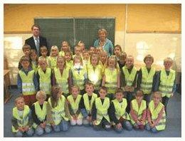 Strahlten mit ihren neuen Signalwesten um die Wette. Erstklässler der Sankt Franziskus Grundschule Twisteden mit ihrer Schulrektorin Andrea Leurs und dem Beigeordneten Marc Buchholz.