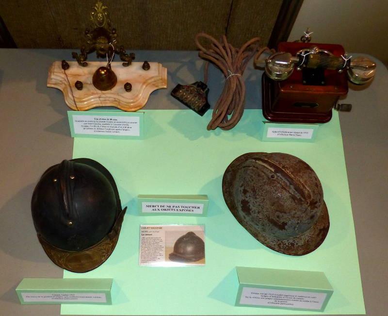 """2 casques """"Adrian"""", 1 téléphone de 1910, une tête d'obus recyclée en encrier"""