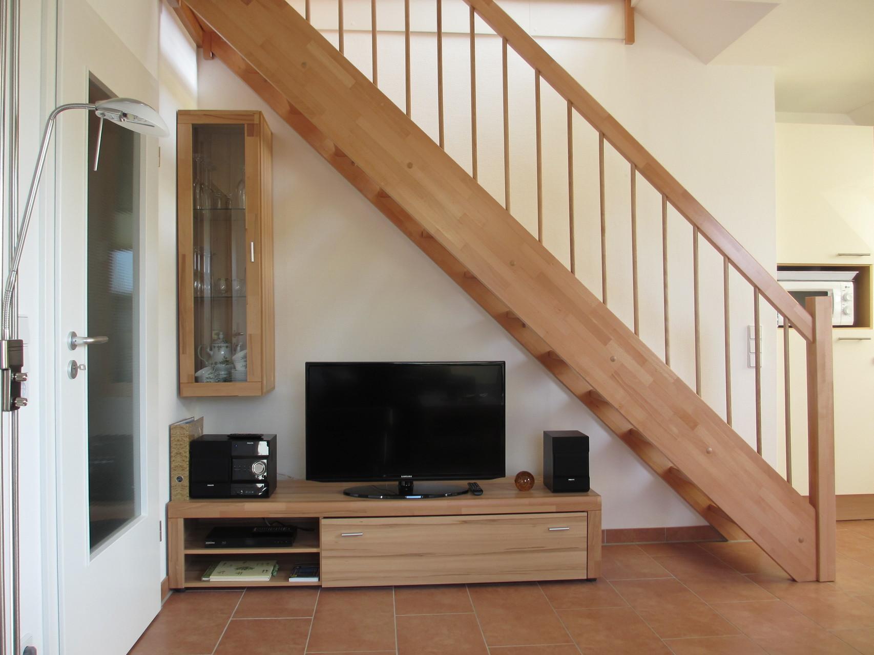 Wohnwand mit Fernseher, Stereoanlage und Treppe zur Galerie