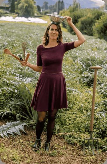 Ariane en robe dans les champs de cardons du GAEC bouquet savoyard avec passoire sur la tête et ustensiles de cuisine dans les mains