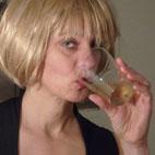 Frau mit blonder Karnevalsperücke, die aus einem Glas trinkt