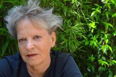 Frau um die Sechzig mit kurzen grauen Haaren, Lippen geschminkt, vor Gebüsch