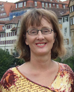 Frau mit halblangen blonden Haaren und Brille, lächelnd, am Neckarufer in Tübingen