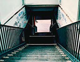 Treppenabstieg zu einer Unterführung, mit Graffiti an den Wänden
