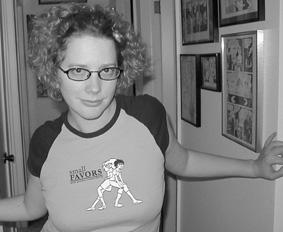 Junge Frau mit blonden Locken und Brille, enges stylishes T-Shirt mit Aufdruck eigener Comic-Zeichnung