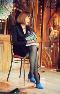 Elegante Frau mit kurzem Kostüm, Halskette und mittelblauen Stilettos liest auf einem Barhocker aus ihrem Buch vor.