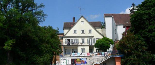 Sudhaus: Hohes weißes Gebäude mit Fensterläden und Giebel, am Geländer Veranstaltungsplakate