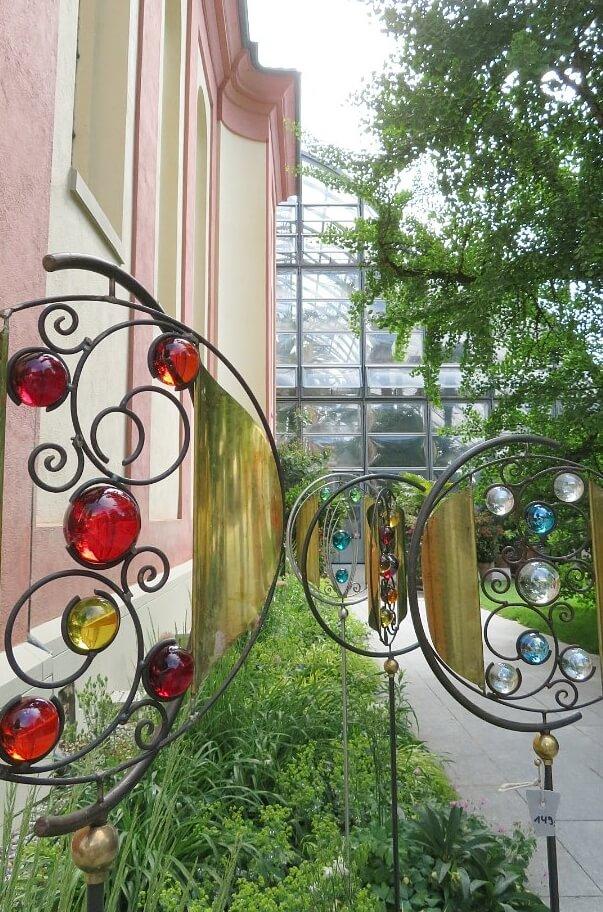 Zauberhafte Kugelbogen gibt es auf dem Stand von keramik-art.de. Diese Garten-Dekoationsobjekte bündeln Licht und Sonne in unzählige Glazpunkte. Im Hintergrund das Palmenhaus der Insel Mainau.