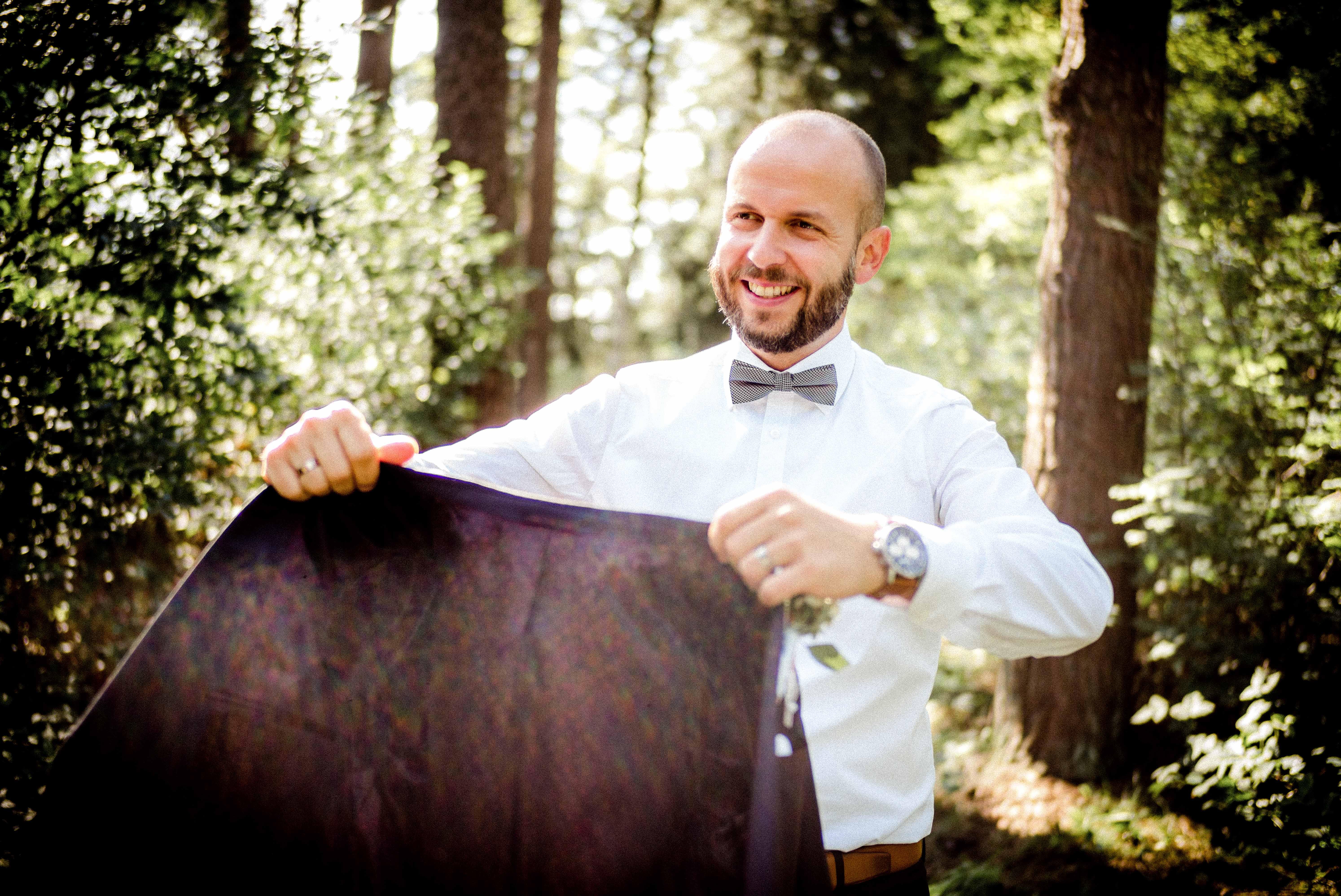 Bräutigam hält Sakko ausgestreckt in den Händen und lächelt dabei