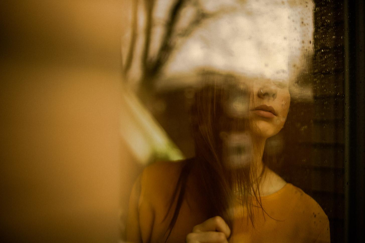 Frau blickt durch ein verregnetes Fenster nach draußen