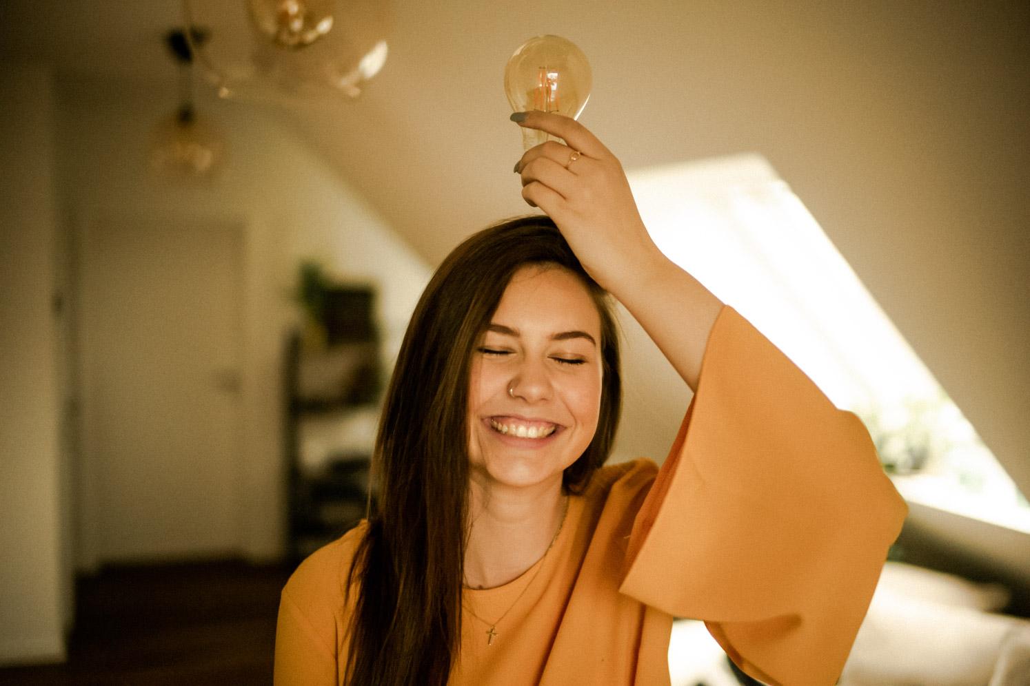 Junge Frau mit Glühbirne auf dem Kopf beim Fotoshooting