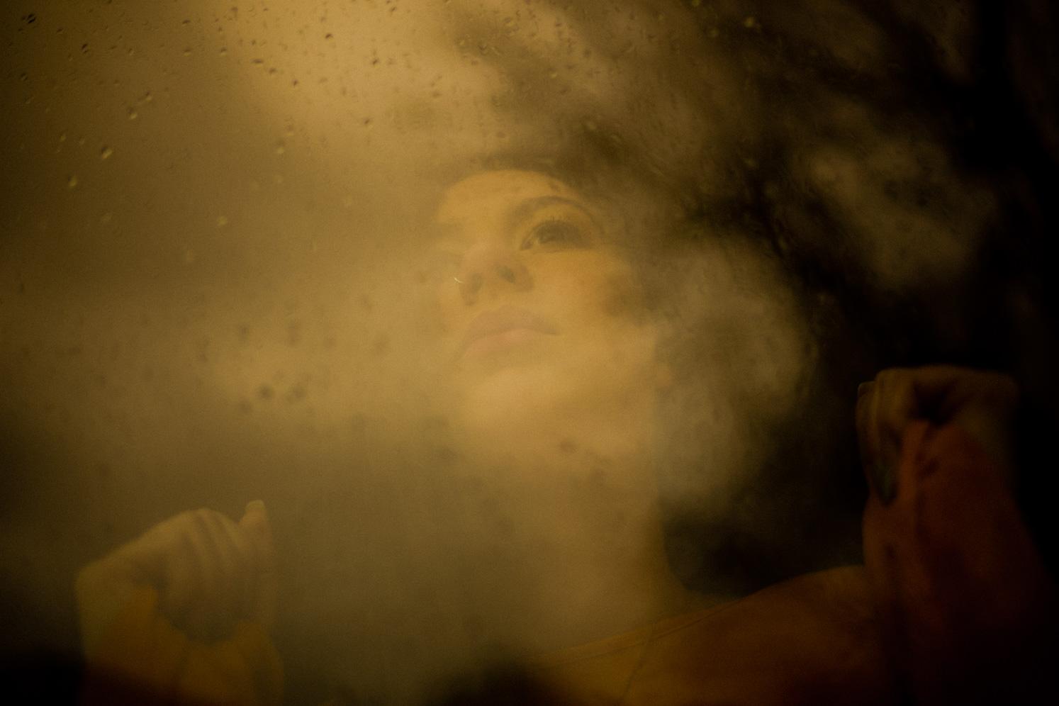 Frau blickt durch ein Fenster nach draußen
