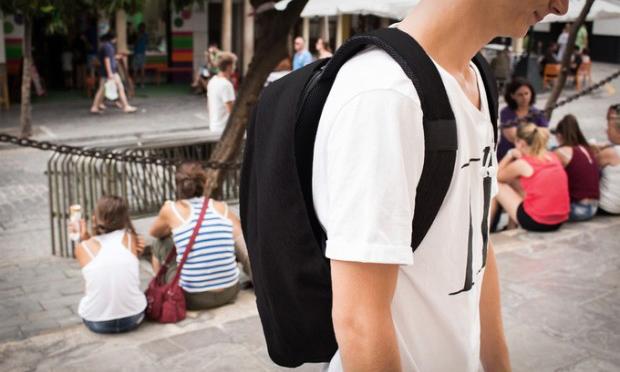 Mann Trägt schwarzer antidiebstahl Rucksack in der Öffentlichkeit