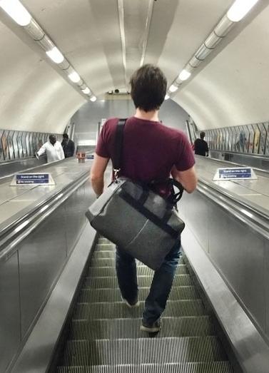 Mann trägt Epirus London Umhängtasche auf Rolltreppe