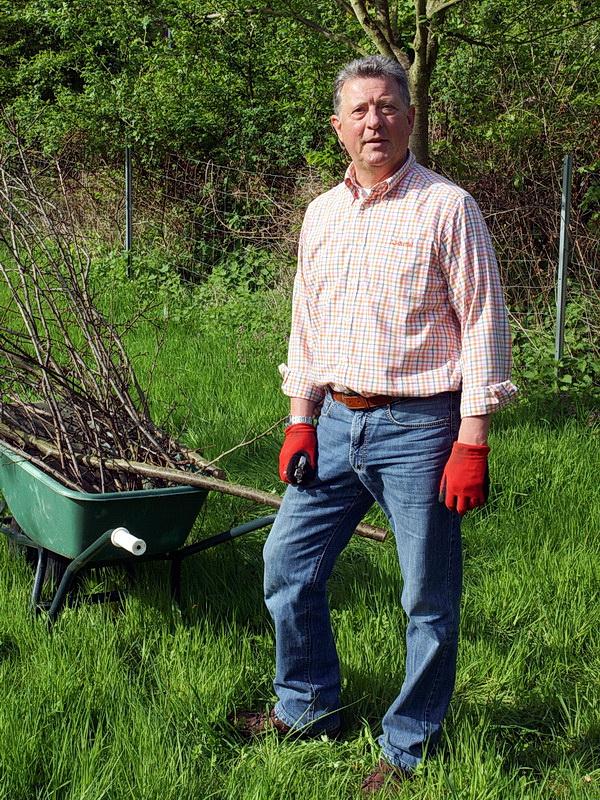 Gerd sammelt den Obstbaumschnitt ein, der noch vom Februar liegen gelieben ist..