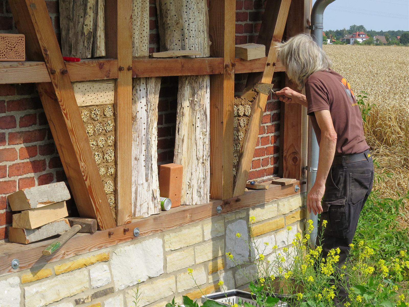 Die mit Bambusstengeln gefüllten Dosen werden von Andreas mit Lehm fest eingebaut