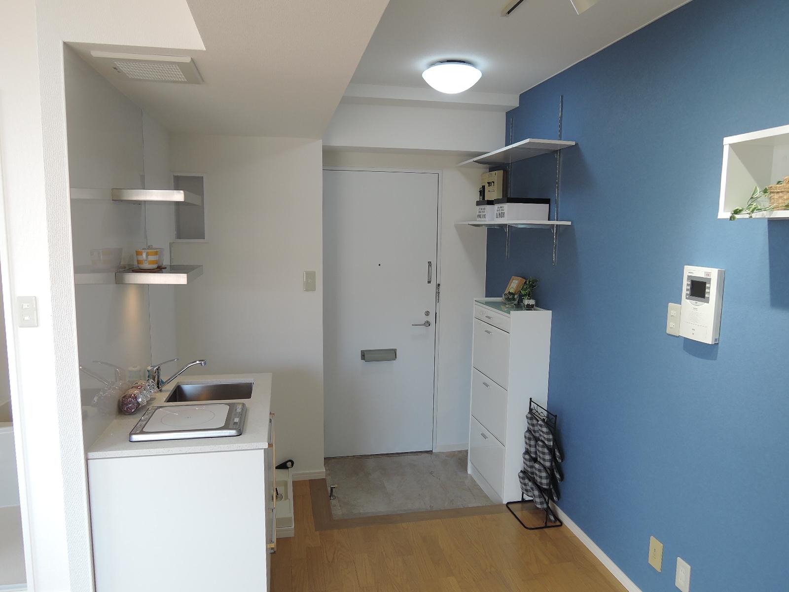 天井・壁・靴入れ・棚等は白で統一、青いアクセントクロスが爽やかです
