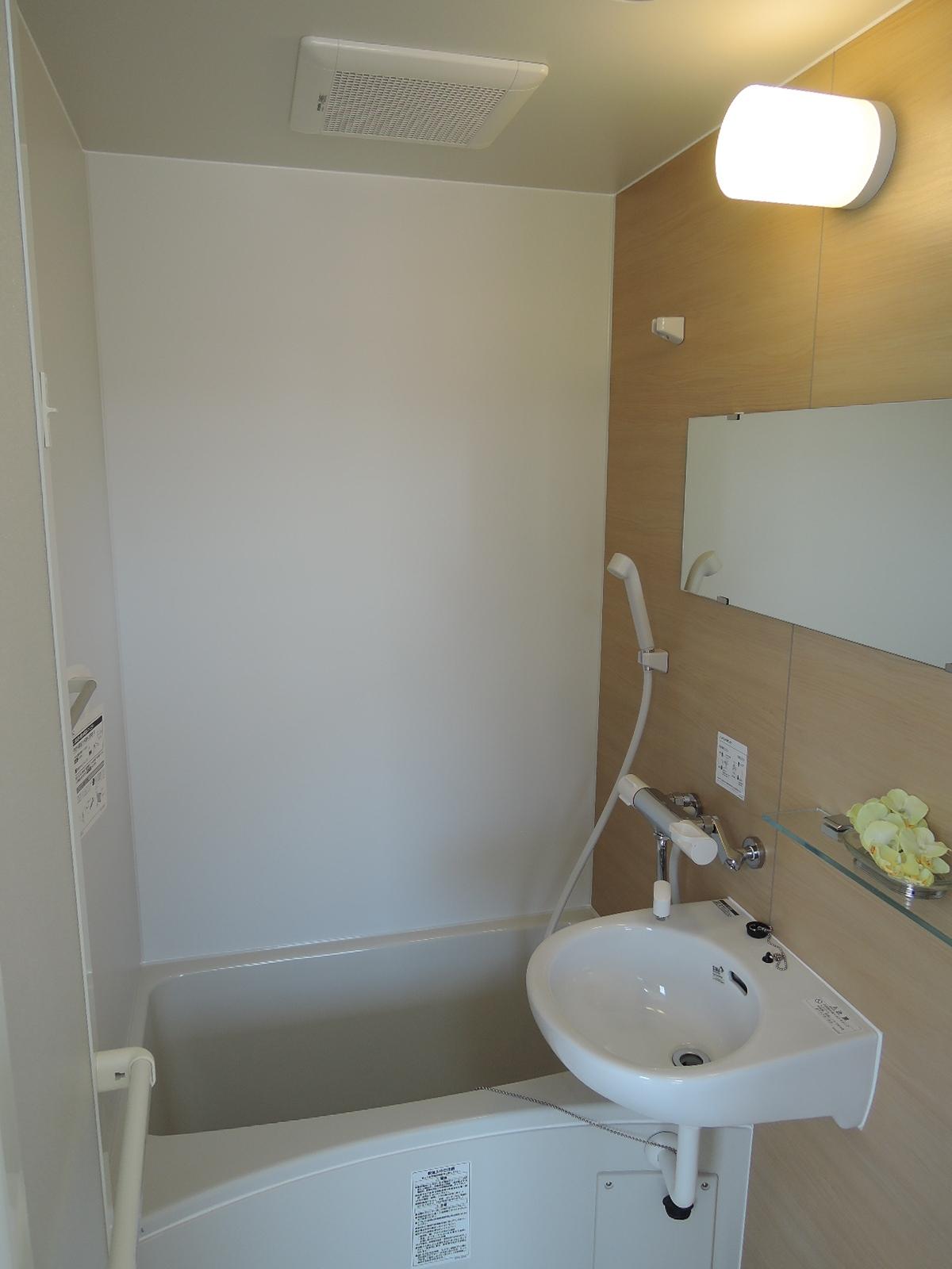 洗面器と横長の大きな鏡付きのバスルーム
