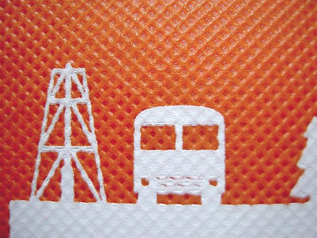 不織布バッグの印刷:オレンジ色の生地に白色シルク印刷の拡大画像※小さな抜き柄はつぶれる可能性があります。
