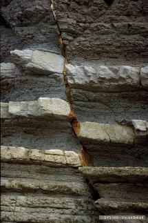 Faille séparant 2 blocs rocheux constitués d'une altérnance de couches grises (marne) et blanches (calcaire). Sources: BIPS banque d'image pédagogiques.