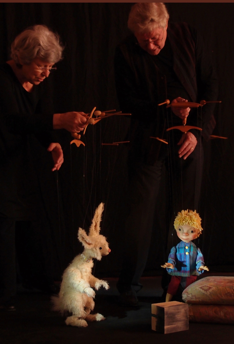 Communication between the puppets necessitates communication between the puppeteers