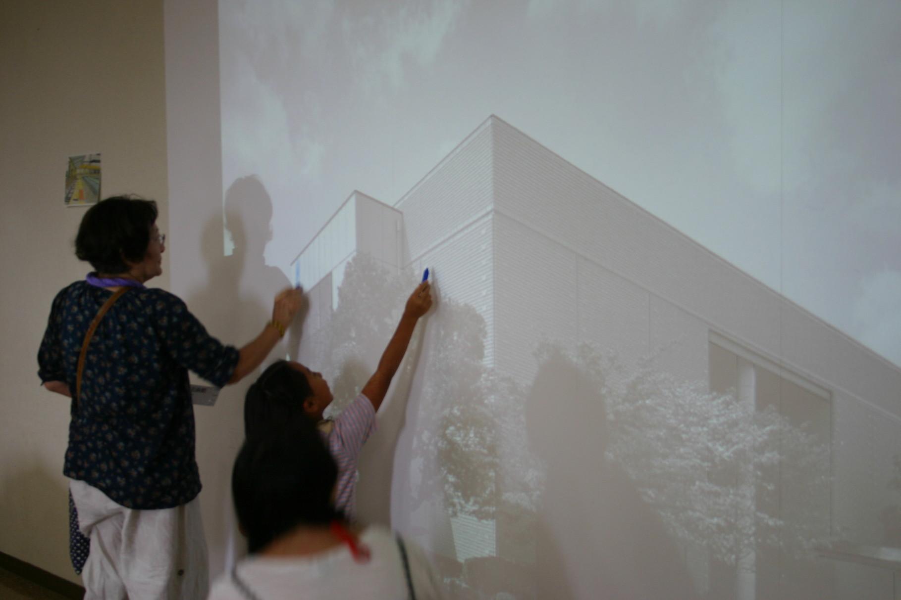 プロジェクターで大きくうつしだした刈谷市美術館の外観にらくがきをする。