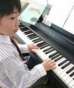 男の子がピアノを弾く写真