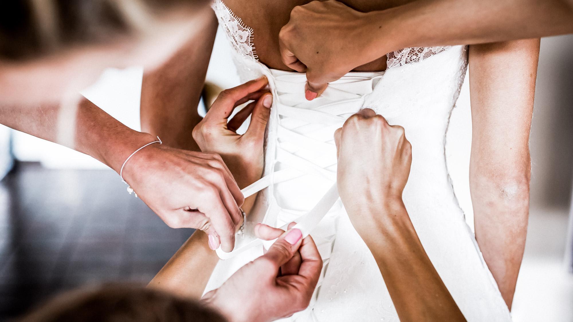 helfende Hände am Brautkleid - FOTOFECHNER