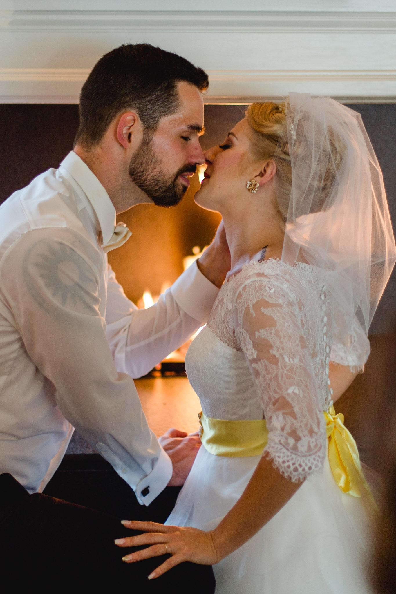 küssendes Brautpaar am Kamin