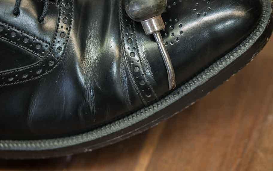 Das Bild zeigt das Hand-Werkzeug, den Stupper, mit dem der Rahmen vor dem Doppeln gestuppt wurde. Bei diesem Schuh ist die Doppelnaht zusätzlich in einem Riss im Rahmen fast nicht sichtbar versenkt.