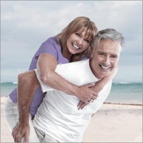 Mann mit starker Schulter trägt Frau am Strand