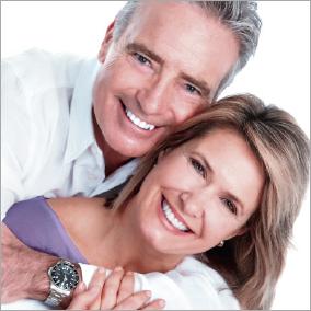 Mann umarmt Frau von hinten. Beide sind fit und fröhlich.
