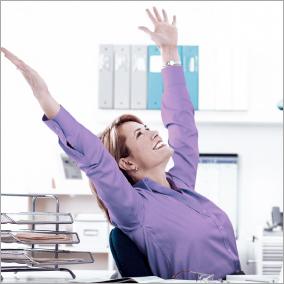 Frau am Computer-Arbeitsplatz reckt Arme nach oben.