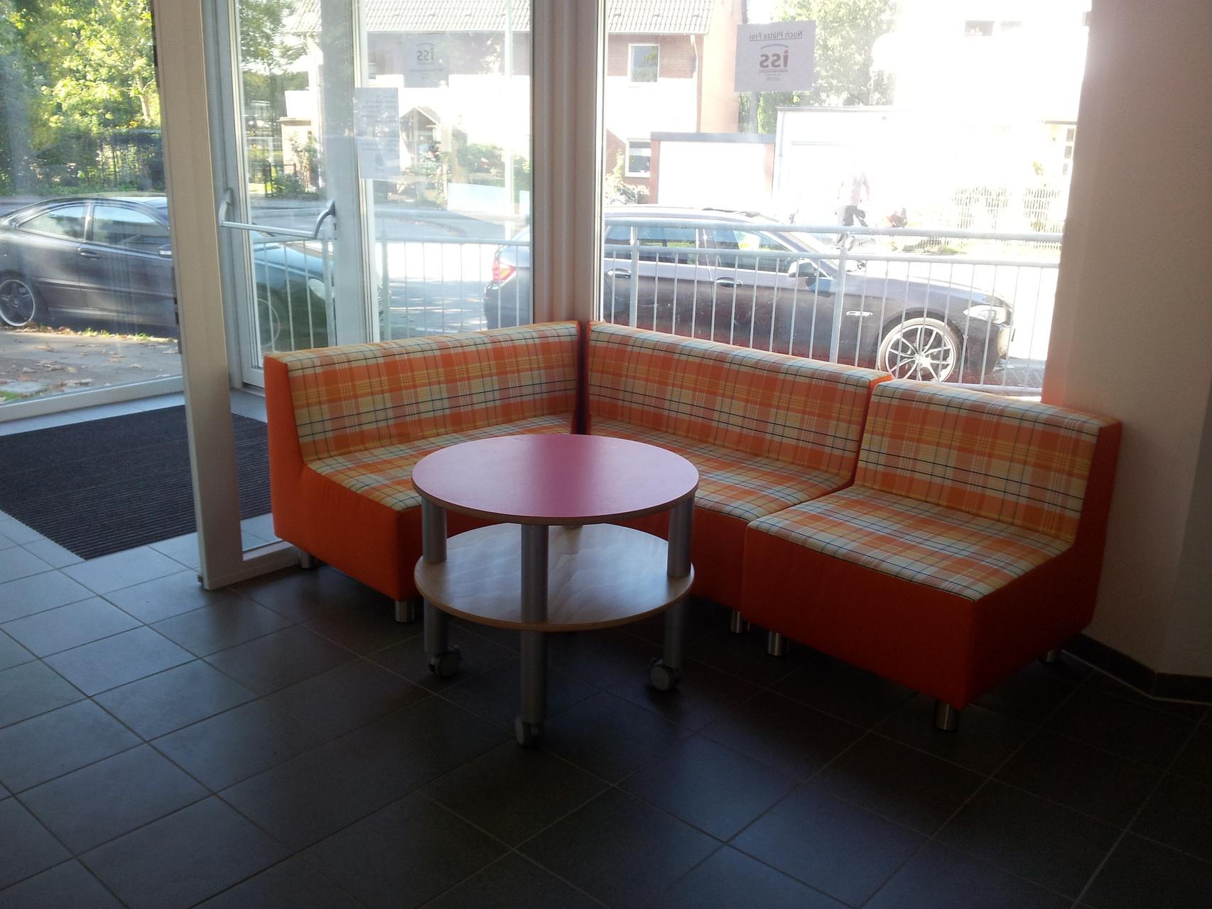 Elternwarteecke mit Sofa und Tisch