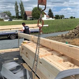 Die ersten Bohlen des Holzhauses in massiver Holzbauweise wurden genau positioniert