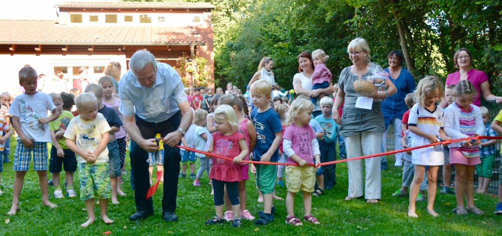 Bürgermeister Hans-Heinrich Barnick gibt den Spielplatz nach dem Durchtrennen des Absperrbandes frei.