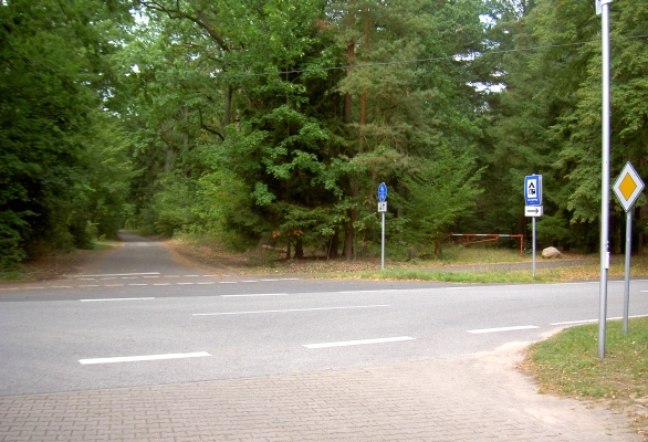 Nah Werbellinsee: Abzweig zum Campingplatz Jatour (Am Spring) nach rechts/vorn. Nach links (hinten im Bild) asphaltierter Weg zur Hinterseite des Hotel-Komplexes mit Blick auf das Jagdschloss Hubertusstock (ca. 70m vom verschlossenen Eisentor entfernt)