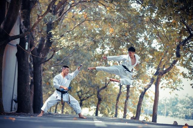 Auf einer Straße und unter Bäumen sind zwei Karatekämpfer. Sie tragen weiße Karateanzüge und üben Sparring.