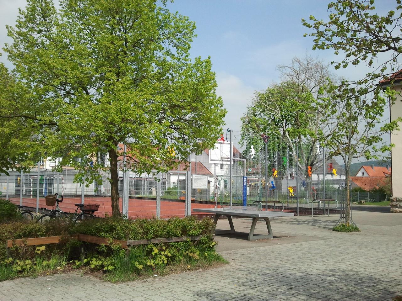 """Schulhof mit """"Käfig"""" im Hintergrund"""