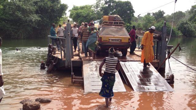 足を濡らしながら渡し船へ向かう女性