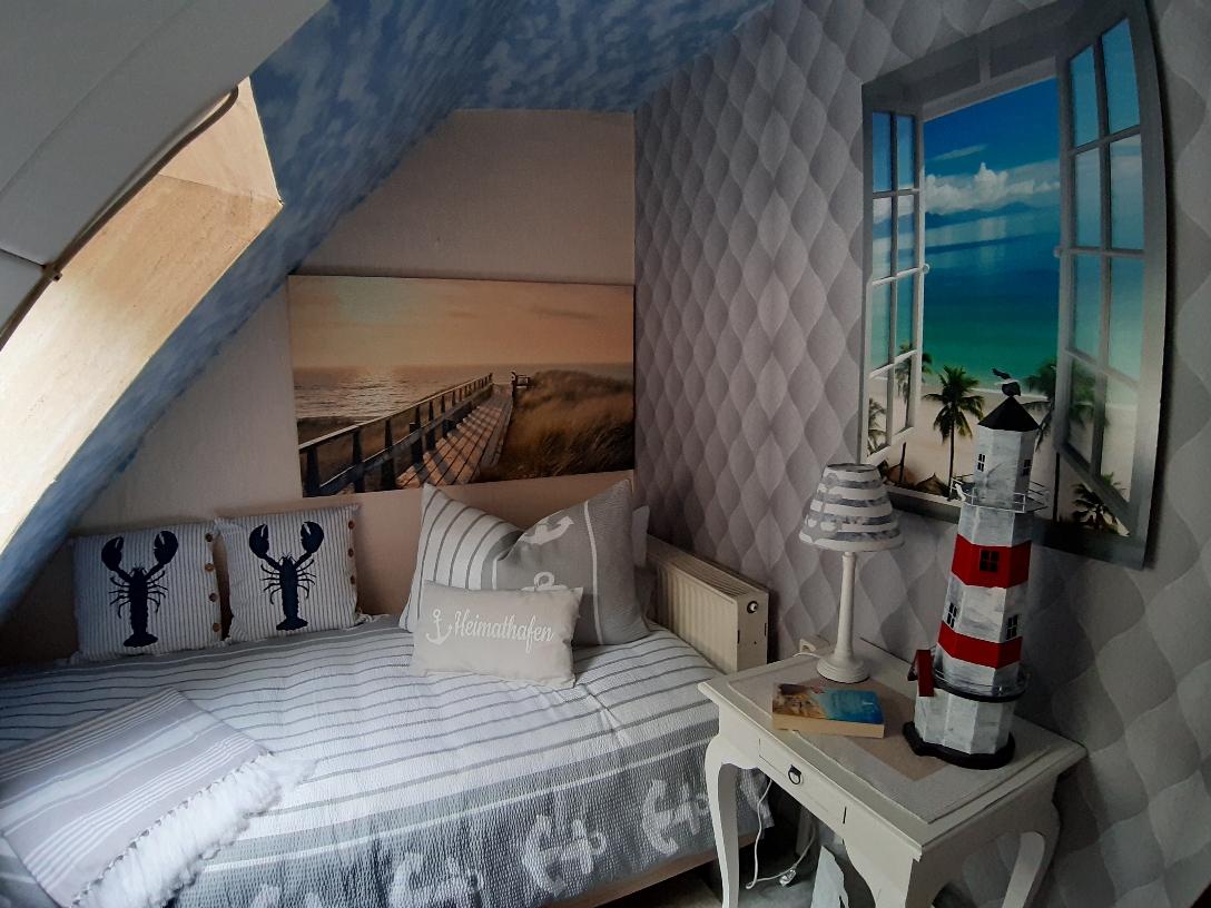 Kleines Zimmer, mit einem Bett und Strandkorbträumen.