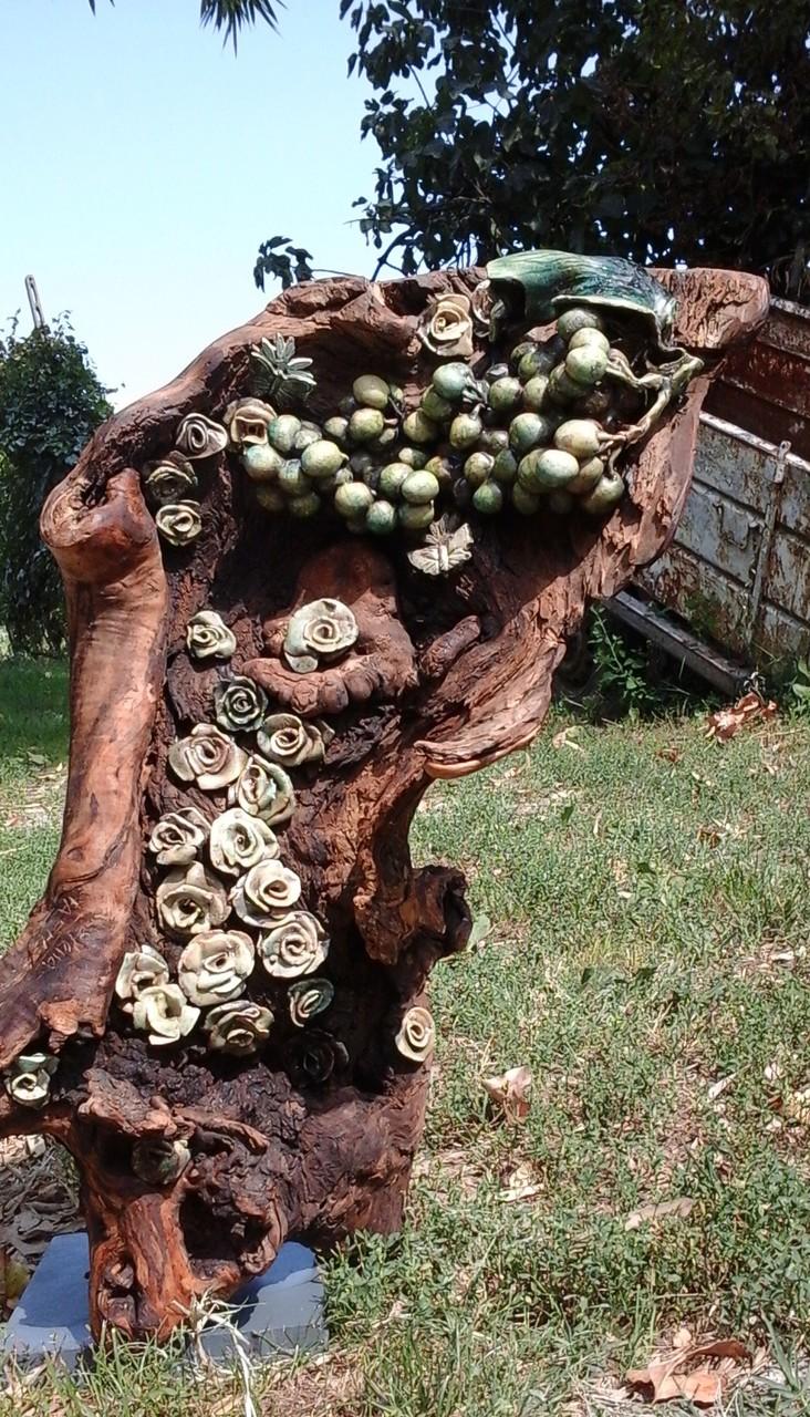 vecchio tronco allestito con grappolo di uva e rose in ceramica raku