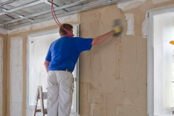 Verputzen einer Wand von einem CMS Fassadengestaltungs Mitarbeiter