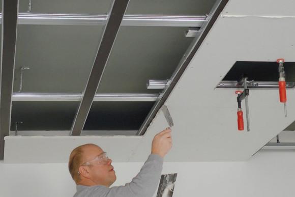 Ein CMS Fassadengestaltung GmbH Mitarbeiter trägt Kleber auf einer Platte